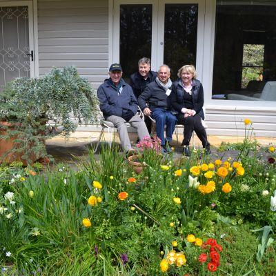 Ladies' Committee representatives sitting on porch behind garden
